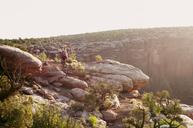 Mountain biker cycling on rocks against clear sky - CAVF06207