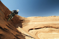 Cyclist riding bicycle on rock formation against clear blue sky - CAVF06213