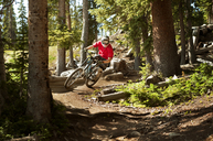 Cyclist riding bicycle on dirt road amidst trees - CAVF06222