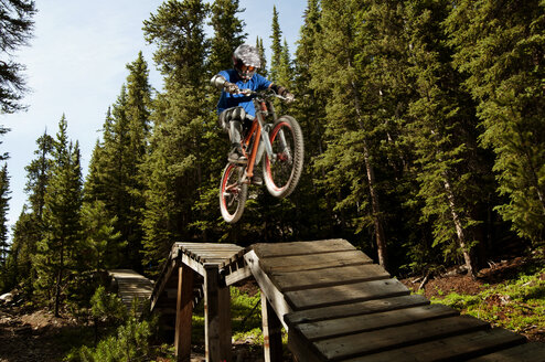 Low angle view of man performing stunt on sports ramp in forest - CAVF06225