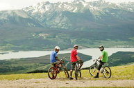 Cyclists with bicycles looking over shoulder - CAVF06231