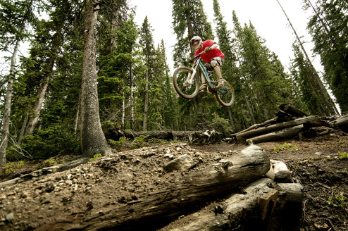 Low angle view of cyclist performing stunt in forest - CAVF06234