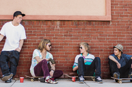 Friends with skateboard talking while sitting against brick wall - CAVF06252
