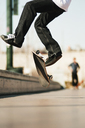 Low section of man jumping with skateboard on footpath - CAVF06258