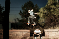 Man with skateboard jumping over friend - CAVF06267