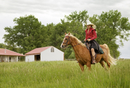 Woman riding on horse against cloudy sky - CAVF06279