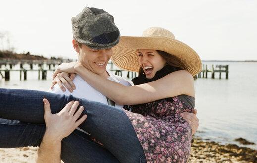 Man lifting woman while walking at beach - CAVF06306