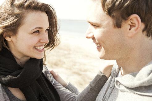 Happy couple standing at beach - CAVF06312