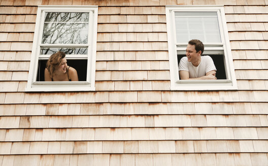 Couple leaning on windows at home - CAVF06321