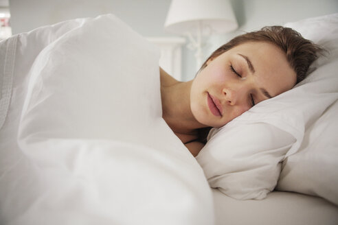 Woman sleeping on bed at home - CAVF06327