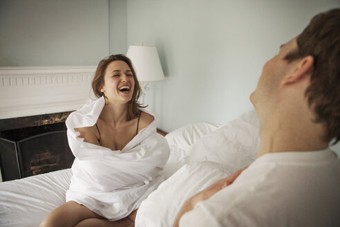 Happy woman wrapped in blanket sitting by man on bed at home - CAVF06336
