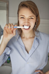 Portrait of woman brushing teeth while standing at home - CAVF06342