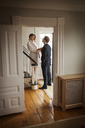 Woman holding man's tie while standing on staircase at home - CAVF06345