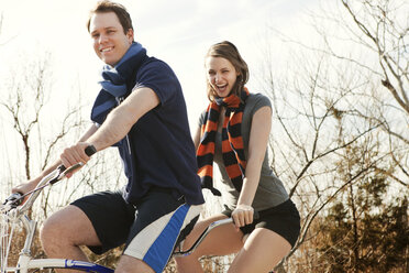 Portrait of cheerful couple riding tandem bicycle against sky - CAVF06351