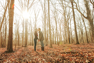 Side view of couple kissing while standing in forest - CAVF06363