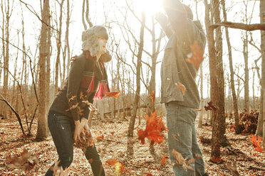 Couple playing with leaves while standing in forest - CAVF06366