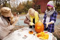 Woman photographing while friends carving Halloween pumpkin at table - CAVF06453