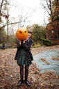 Woman carrying Halloween pumpkin while standing on field - CAVF06456