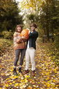 Portrait of couple carrying Halloween pumpkin while standing on field - CAVF06459