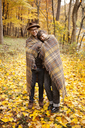 Portrait of couple wrapped in blanket while standing on field - CAVF06471
