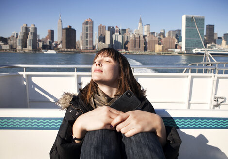 Woman relaxing while traveling in ferry against buildings - CAVF06483