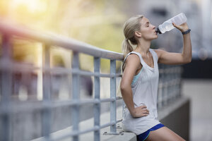 Woman drinking water after exercising on city street - CAIF15177
