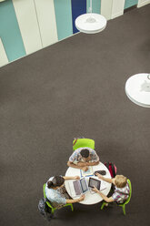 Overhead view of student doing homework, using laptop and digital tablet - CAIF15222