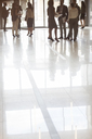 Group of business people standing in office, reflections in tiled floor - CAIF15240