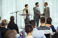 Businessmen shaking hands during presentation in conference room, businesswoman smiling - CAIF15249