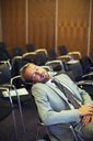 Businessman sleeping in conference room - CAIF15261