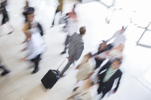 Businessman walking through lobby of public building towards exit, wheeling trolley case - CAIF15273