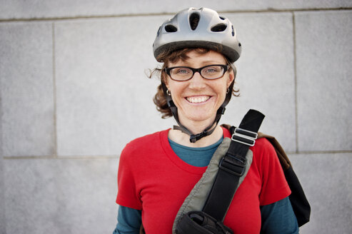 Portrait of woman in cycling helmet against building - CAVF06564