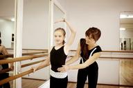 Happy teacher guiding student in dance studio - CAVF06591