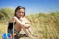 Portrait of happy girl sitting on sand against clear sky - CAVF06732