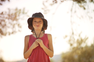 Portrait of happy girl in hat standing against sky on sunny day - CAVF06747