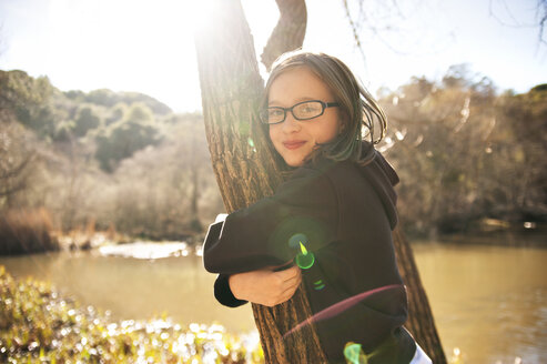 Portrait of happy girl holding tree trunk in forest - CAVF06774
