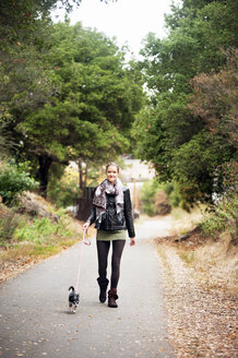 Portrait of woman with dog walking on road - CAVF06810