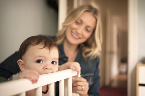 Mother looking at baby boy in crib at home - CAVF06906
