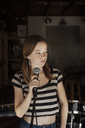 Girl looking away while standing by microphone - CAVF06939