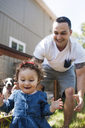 Happy father playing with daughter in backyard - CAVF06957