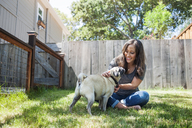Woman playing with pug while sitting on grassy field in backyard - CAVF06960