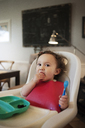 Baby girl eating while sitting in high chair at home - CAVF06969