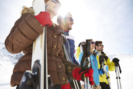 Friends standing with skis on mountain top - CAIF15312