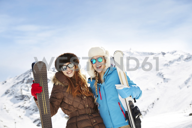 Friends holding skis on mountain top together - CAIF15315