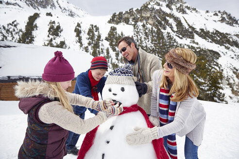 Family building a snowman together - CAIF15378