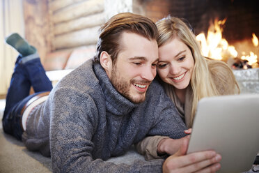 Couple using digital tablet by fireplace together - CAIF15405