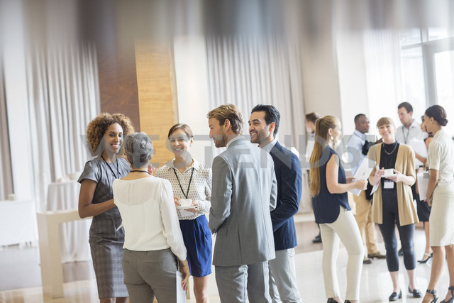 Group of business people standing in hall, smiling and talking together - CAIF15417 - Sam Edwards/Westend61