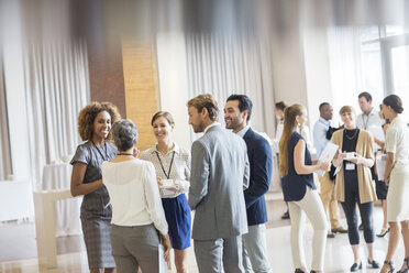 Group of business people standing in hall, smiling and talking together - CAIF15417