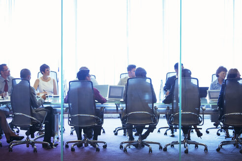 Business people having meeting in conference room, sitting with laptops and discussing - CAIF15447
