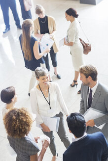 Businesswoman talking to conference participants, standing in lobby of conference center - CAIF15471